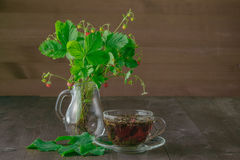 Cup of tea and strawberry bouquette Stock Photos