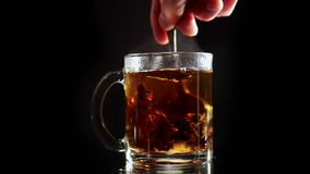 A Cup of Tea With Sugar Mixed. The Transparent of Glass Cup of Tea Mix, Granulated Sugar is Dissolved. Black Background stock footage