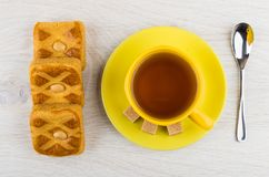 Cup of tea, sugar on saucer, cookies with marzipan, teaspoon. On table. Top view stock photography