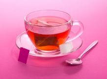 Cup of tea and sugar on a saucer. A teaspoon, on a pink background Royalty Free Stock Image