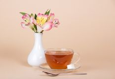 Cup of tea and sugar on a saucer. A teaspoon, vase with the flowers, on a beige background stock photography