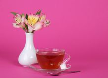 Cup of tea and sugar on saucer, teaspoon, vase. Cup of tea and sugar on a saucer, a teaspoon, vase with the flowers, on a pink background royalty free stock photography