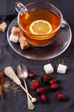 Cup of tea with sugar and spices. Glass cup of tea with sugar cubes, berries and spices, served over dark gray textile Royalty Free Stock Photos