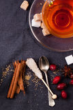 Cup of tea with sugar and spices. Top view on cup of tea with sugar cubes, berries and spices, served over dark gray textile Stock Photo