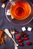 Cup of tea with sugar and spices. Top view on cup of tea with sugar cubes, berries and spices, served over dark gray textile. See series Royalty Free Stock Photo