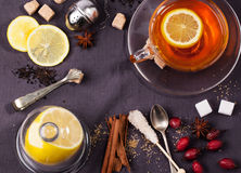 Cup of tea with sugar and spices. Top view on cup of tea with sugar cubes,lemon, berries and spices, served over dark gray textile. See series Royalty Free Stock Photo