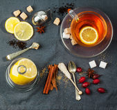 Cup of tea with sugar and spices. Top view on cup of tea with sugar cubes, lemon, berries and spices, served over dark gray textile. See series Stock Image