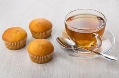 Cup of tea, sugar and teaspoon, muffins on table. Cup of tea, sugar and teaspoon, muffins on wooden table Royalty Free Stock Image
