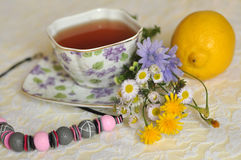 A cup of tea, summer yellow and blue field flowers, a lemon and a necklace on an elegant lace surface Stock Image