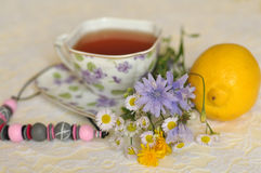 A cup of tea, summer yellow and blue field flowers, a lemon and a necklace on an elegant lace surface Royalty Free Stock Image
