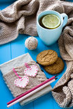 A cup of tea in sweater with lemon, old notebook with hearts. Of felt, beige knitted blanket and spokes lie on blue background Royalty Free Stock Images