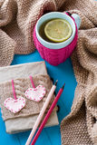 A cup of tea in sweater with lemon, old notebook with hearts. Of felt, beige knitted blanket and spokes lie on blue background Stock Photography
