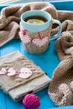 A cup of tea in sweater, old notebook with hearts of felt, beige. A cup of tea in sweater with lemon, old notebook with hearts of felt, beige knitted blanket and Royalty Free Stock Images