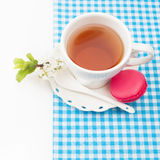 Cup of tea and sweet and colourful french macaroon and a cherry Stock Photos