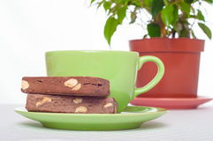 Cup of tea and sweets on books stack with indoor plant at backgr Stock Images