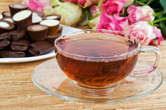 Cup of tea with sweets and flowers Stock Image