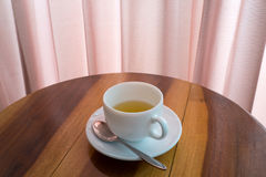 Cup of tea on the table. Cup of tea with teaspoon on the wooden table Stock Photos