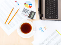 Cup of tea on table with tools in modern office Stock Image