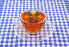 Cup of tea on tablecloth Stock Photos