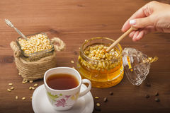 A cup of tea with tasty honey and pine nuts. Dessert. Stock Photo