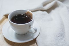 Cup of tea with tea bag dipping in hot water on wooden and cotton fabric stock photography