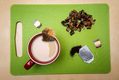 Cup of tea from tea-bag with milk on green cutting board with mushrooms Stock Photo