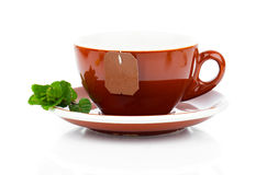 Cup of tea with tea bag and mint plant Stock Photos