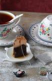 A cup of tea and tea bag on a table Stock Photos