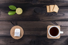Cup of tea with tea cookies, fresh lime and tea bag on wooden table. Cup of tea with tea cookies, fresh lime and tea bag on wooden background Royalty Free Stock Photos