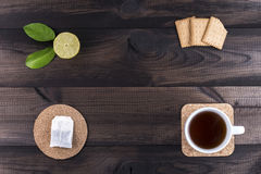 Cup of tea with tea cookies, fresh lime and tea bag on woodentable Stock Photography