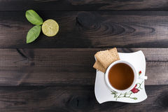 Cup of tea with tea cookies and fresh lime on wooden table. Cup of tea with tea cookies and fresh lime on wooden background Royalty Free Stock Photography