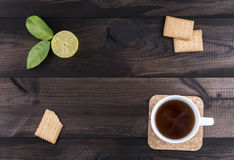 Cup of tea with tea cookies and fresh lime on wooden table. A cup of tea with tea cookies and fresh lime on wooden background Royalty Free Stock Image