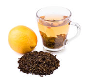 A cup of tea. A tea cup isolated on a white background. A beautiful cup with natural green tea leaves and a whole bright lemon. Stock Image