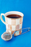 Cup of tea and tea infuser Stock Photos