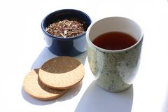 Cup of tea with tea leaves in a bowl and biscuits at the side. Modern minimalistic image. Cup of tea with tea leaves in a bowl and biscuits at the side. Modern royalty free stock photography
