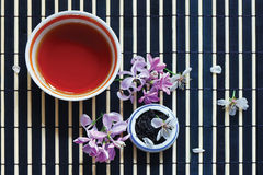 Cup of tea, tea leaves, cherry blossoms and lilac Royalty Free Stock Photography
