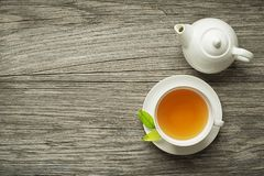Cup of tea with tea pot. Cup of green and herbs tea served with tea pot on wooden table royalty free stock photos