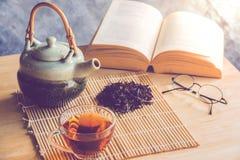 A cup of tea with tea pot and dride tea leaf with reading book. Close up a cup of tea with tea pot and dride tea leaf with reading book on table stock photo