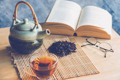 A cup of tea with tea pot and dride tea leaf with reading book. Close up a cup of tea with tea pot and dride tea leaf with reading book on table royalty free stock images