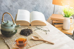 A cup of tea with tea pot and dride tea leaf with reading book. On table royalty free stock photography