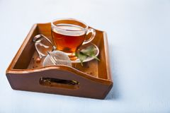 Cup of tea and a tea strainer. On a brown wooden tray. Brewing tea Royalty Free Stock Photos