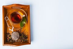Cup of tea and a tea strainer. On a brown wooden tray, top view. Brewing tea Royalty Free Stock Photos