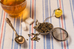 A cup of tea with tea strainer on a table cloth Stock Photography