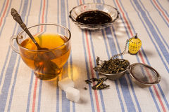 A cup of tea with tea strainer on a table cloth Stock Images