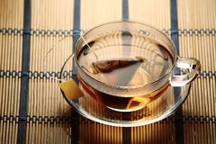 Cup of tea with teabag. Glass cup of tea with teabag on straw table cloth Royalty Free Stock Image