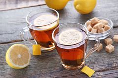 Cup of tea with teabag. And lemon on wooden table Stock Images