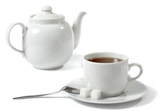 Cup of tea and teapot. Cup of tea, teapot, spoon and sugar isolated over white Stock Photos