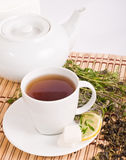 Cup of tea and teapot. Green tea with herbs and lemon on bamboo mat background Royalty Free Stock Photography