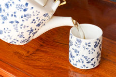 A cup of tea with teapot in the background Stock Images