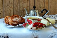 Cup of tea, teapot and  buns Stock Photos